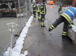 Einsatzkräfte legen Sandsäcke aus