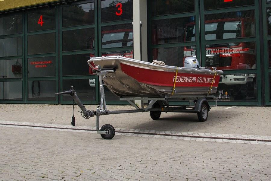 Hier sehen Sie den Feuerwehranhänger mit Boot vor der Fahrzeughalle der Abteilung Oferdingen