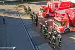 Der Grundausbildungslehrgang tritt vor den Feuerwehrfahrzeugen an