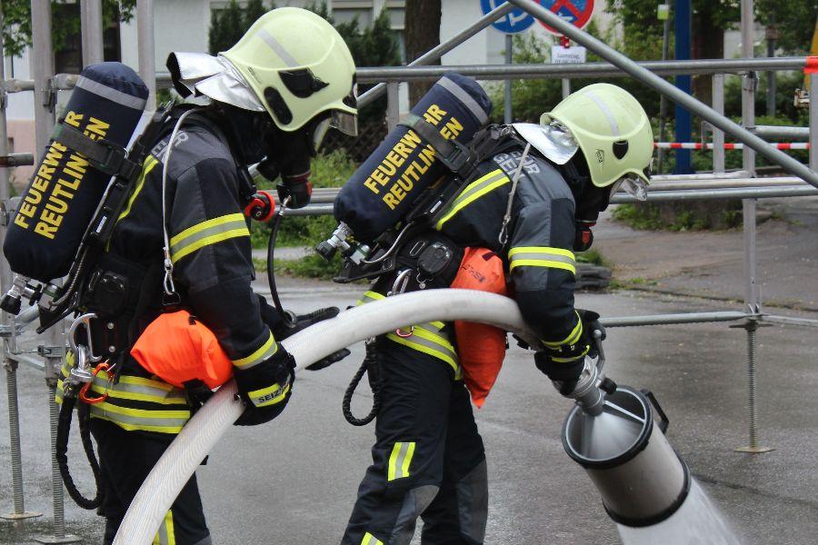 zwei Feuerwehrmänner unter Atemschutz bereiten eine Schaumeinsatz vor