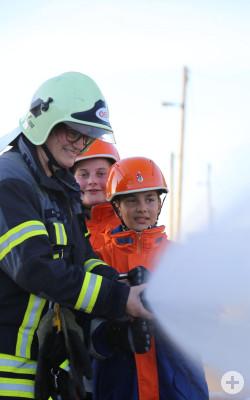 Wasser aus Strahlrohr mit Jugendlichen und Übungsleiter