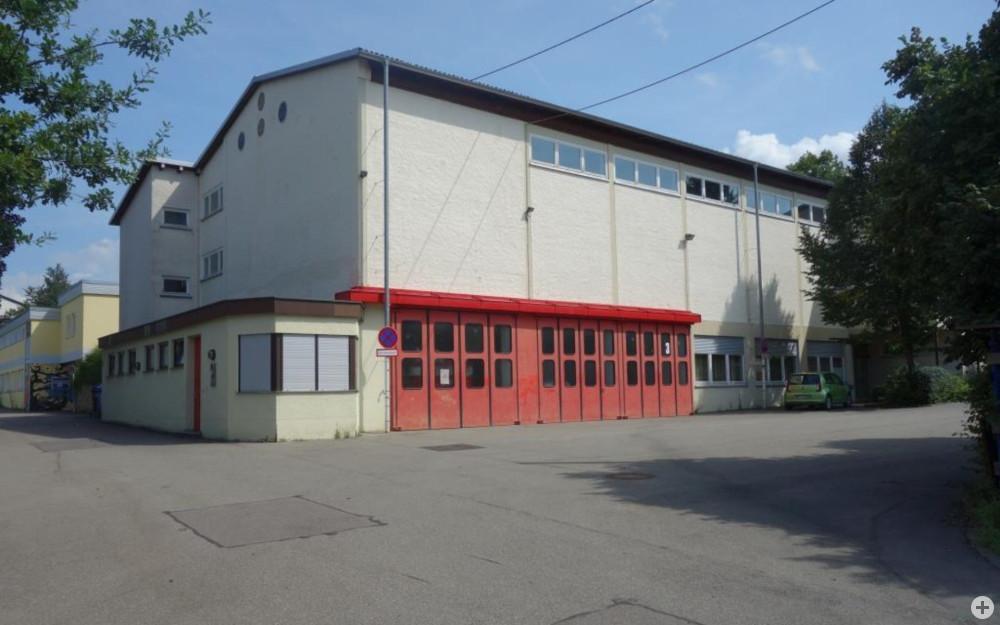 Ansicht der Gemeindehalle von Süden mit den roten Toren der Feuerwehr