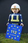 Playmobilfigur mit einem Schild auf dem die Notrufnummer 112 zu sehen ist