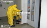 Symbolbild für Gefahrgut, man sieht auf dem Bild zwei Feuerwehrmänner in Schutzanzügen vor einem Chemieschrank.