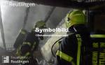 Symbolbild für Brandeinsatz, man sieht auf dem Bild zwei Feuerwehrmänner bei einem Brand in einem Dachstuhl.