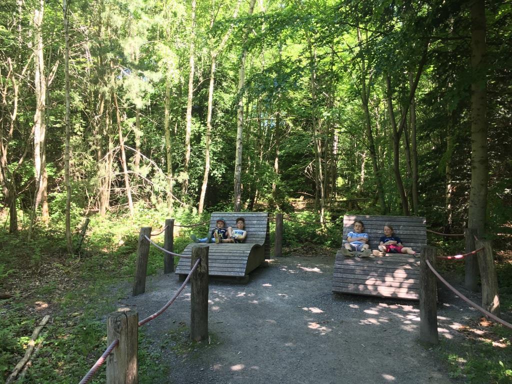Kinder ruhen sich auf Holzliegen auf dem Erlebnispfad aus