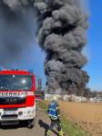 Großbrand in Mittelstadt - Im Vordergrund ist ein Feuerwehrauto zu sehen, daneben ein Feuerwehrmann und im Hintergrund eine große dunkle Rauchwolke
