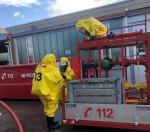 Drei Einsatzkräfte im Chemikalienschutzanzug bei der Übung an der Gefahrgutübungsanlage