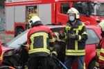 3 Feuerwehrleute zerschneiden einen Personenkraftwagen als Übung zur Befreiung von Personen