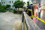 Feuerwehrleute auf einer Brücke an der von Starkregen gefüllten Echaz