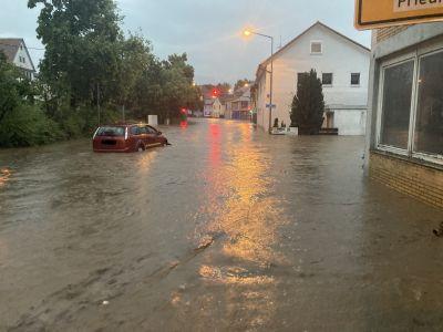 Ein steckengebliebenes Fahrzeug steht auf einer Straße, die unter Wasser steht.