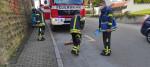 Hier zu sehen das Löschgruppenfahrzeug bei der Verkehrsabsicherung und 4 Feuerwehrmänner beim beseitigen einer Ölspur