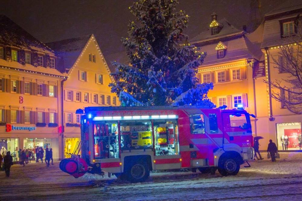 hier sieht man das Hilfeleistungslöschgruppenfahrzeug der Berufsfeuerwehr mit Blaulicht und offenen Rolläden auf dem Marktplatz vor dem Weihnachtsbaum