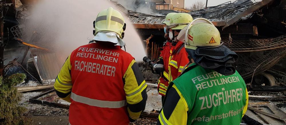 3 Einsatzkräfte der Gefahrstoffeinheit von hinten bei einer Lagebesprechnung beim Großbrand einer Firma in Wittlingen