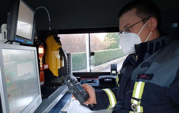 Feuerwehrmann liest Messwerte von Messgerät in seiner Hand ab