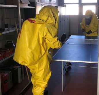 Zwei Einsatzkräfte im Chemikalienschutzanzug beim Tischtennis spielen